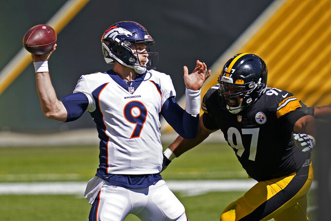 Denver Broncos quarterback Jeff Driskel (9) passes under pressure from Pittsburgh Steelers defensive tackle Cameron Heyward (97) during the first half of an NFL football game, Sunday, Sept. 20, 2020, in Pittsburgh. (AP Photo/Keith Srakocic)