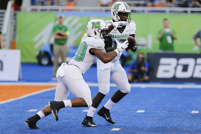 Marshall quarterback Isaiah Green, right, hands off the ball to running back Brenden Knox, left, during the first half of an NCAA college football game against Boise State in Boise, Idaho, Friday, Sept. 6, 2019. (AP Photo/Otto Kitsinger)