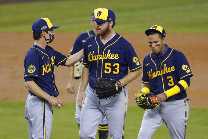 Milwaukee Brewers manager Craig Counsell, left, removes starting pitcher Brandon Woodruff (53) during the fifth inning in Game 2 of the team's National League wild-card baseball series against the Los Angeles Dodgers on Thursday, Oct. 1, 2020, in Los Angeles. (AP Photo/Ashley Landis)