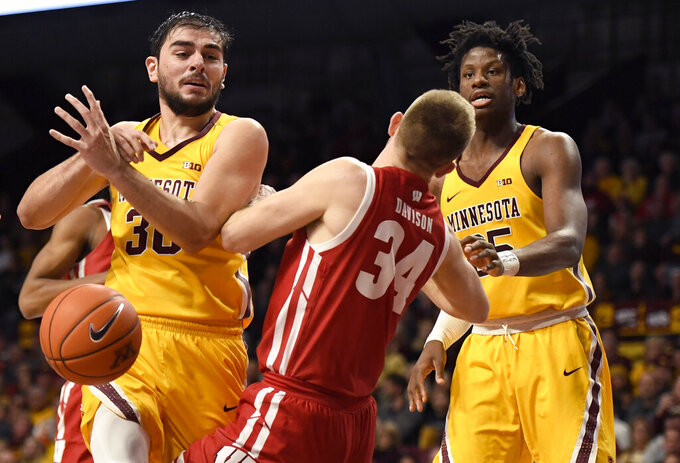 Minnesota's Alihan Demir (30) loses the ball as he collides with Wisconsin's Brad Davison (34), while Minnesota's Daniel Oturu (25) watches during the first half of an NCAA college basketball game Wednesday, Feb. 5, 2020, in Minneapolis. Davison was called for a foul on the play. (AP Photo/Hannah Foslien)