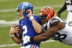New York Giants quarterback Colt McCoy (12) is tackled by Cincinnati Bengals defensive end Carl Lawson (58) during the second half of NFL football game, Sunday, Nov. 29, 2020, in Cincinnati. (AP Photo/Aaron Doster)