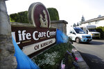 FILE - In this March 18, 2020 file photo, a vehicle leaves the Life Care Center in Kirkland, Wash. The long-term care facility was the site of the nation's first deadly COVID-19 cluster and state authorities said Wednesday that 61% of coronavirus deaths in Washington have been at long-term care facilities. (AP Photo/Elaine Thompson, File)