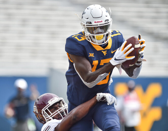 West Virginia wide receiver Sam James (13) catches a pass for a touchdown against Eastern Kentucky during an NCAA college football game on Saturday, Sept. 12, 2020, in Morgantown, W.Va.  (William Wotring/The Dominion-Post via AP)