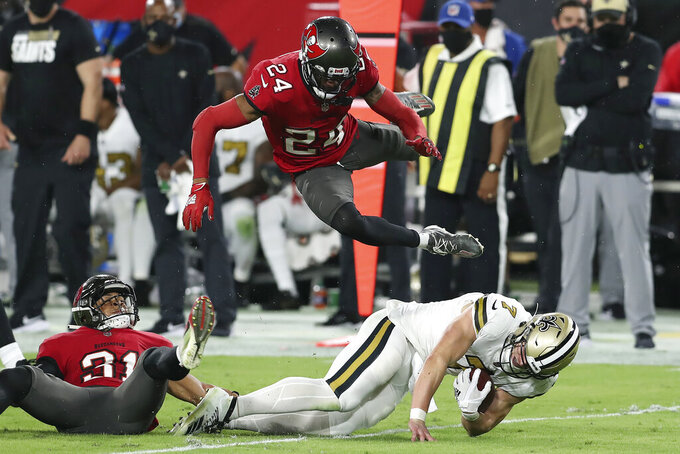 Tampa Bay Buccaneers cornerback Carlton Davis (24) flies through the air as he teams up with strong safety Antoine Winfield Jr. (31) to take down New Orleans Saints quarterback Taysom Hill (7) during the first half of an NFL football game Sunday, Nov. 8, 2020, in Tampa, Fla. (AP Photo/Mark LoMoglio)