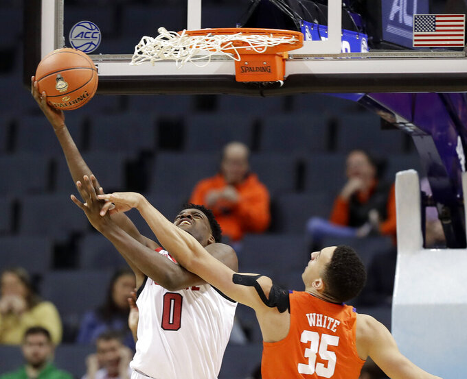 North Carolina State's DJ Funderburk (0) is fouled by Clemson's Javan White (35) during the first half of an NCAA college basketball game in the Atlantic Coast Conference tournament in Charlotte, N.C., Wednesday, March 13, 2019. (AP Photo/Chuck Burton)
