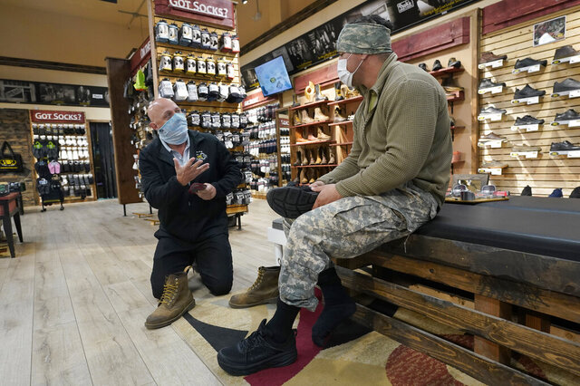 Patrick Marks, left, helps customer Jesus Chavez at Beck's Shoes in the Sutter County committee of Yuba City, Calif., Tuesday, Nov. 17, 2020. Gov. Gavin Newsom announced Monday that due to the rise of COVID-19 cases, Sutter was among the counties that has been moved to the state's most restrictive set of rules, which prohibit indoor dining and requiring people to wear face masks in public. The new rules began on Tuesday. (AP Photo/Rich Pedroncelli)