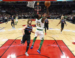 Boston Celtics guard Kyrie Irving (11) shoots the ball as Chicago Bulls center Robin Lopez (42) defends him during the first half of an NBA basketball game Saturday, Feb. 23, 2019, in Chicago. (AP Photo/David Banks)
