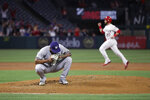 Milwaukee Brewers starting pitcher Freddy Peralta squats on the mound after giving up a three-run home run to Los Angeles Angels' Tommy La Stella during the first inning of a baseball game Tuesday, April 9, 2019, in Anaheim, Calif. In the background is Angels' Jonathan Lucroy. (AP Photo/Jae C. Hong)
