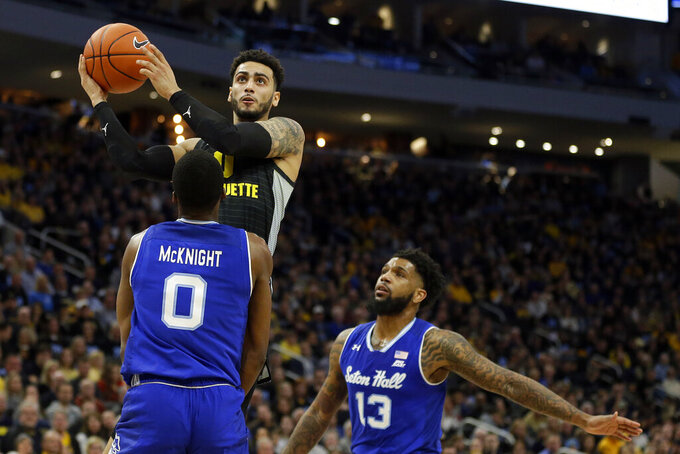 Marquette's Markus Howard is called for a charging foul against Seton Hall's Quincy McKnight during the first half of an NCAA college basketball game Saturday, Feb. 29, 2020, in Milwaukee. (AP Photo/Aaron Gash)
