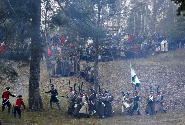 Men dressed as 1812-era Russian and French soldiers re-enact a staged battle in the town of Borisov, 70 km (44 miles) east of Minsk, Belarus, Saturday, Nov. 23, 2019, to mark the 207th anniversary of the Berezina battle during Napoleon's army retreat from Russia. (AP Photo/Sergei Grits)