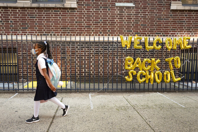 """A girl passes a """"Welcome Back to School"""" sign as she arrives for the first day of class at Brooklyn's PS 245 elementary school, Monday, Sept. 13, 2021, in New York. Classroom doors are swinging open for about a million New York City public school students in the nation's largest experiment of in-person learning during the coronavirus pandemic. (AP Photo/Mark Lennihan)"""