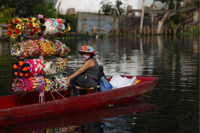 A flower crown vendor waits in her boat for revelers passing in colorfully painted wooden boats known as trajineras at the Nuevo Nativitas dock, as it opens once again to tourists and revelers amidst the ongoing new coronavirus pandemic, the Xochimilco borough of Mexico City, Friday, Aug. 21, 2020. Though traffic was light on the first day back after being closed for several months, gondoliers, handicraft sellers, and food and drink vendors said they were happy to be back at work and to have the chance to earn some money. (AP Photo/Rebecca Blackwell)