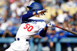 Los Angeles Dodgers' Mookie Betts hits a double against the Chicago Cubs during the first inning of a baseball game in Los Angeles, Saturday, June 26, 2021. (AP Photo/Alex Gallardo)