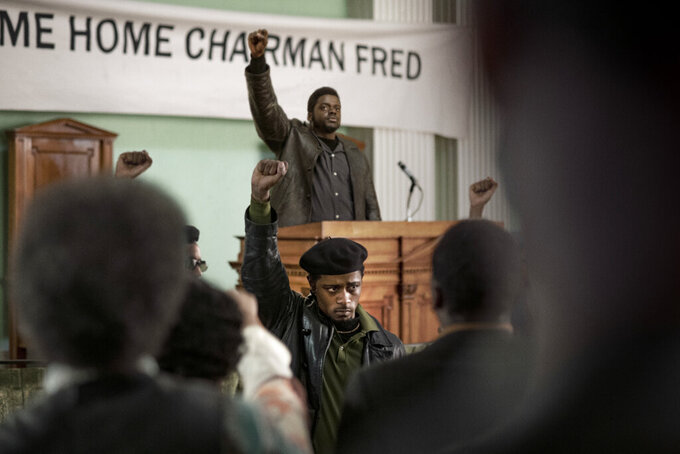 """This image released by Warner Bros. Pictures shows Lakeith Stanfield, foreground center, and Daniel Kaluuya, background center, in a scene from """"Judas and the Black Messiah."""" The film will release in theaters and on HBO Max on Friday. (Warner Bros. Pictures via AP)"""