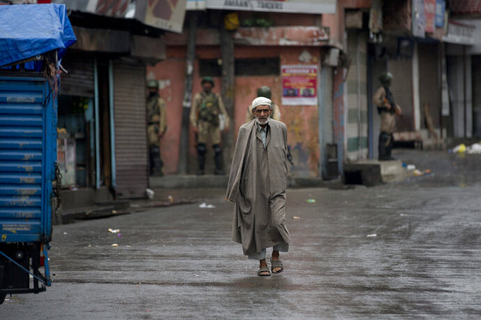 A Kashmiri man walks as Indian paramilitary soldiers stand guard during security lockdown in Srinagar, Indian controlled Kashmir, Wednesday, Aug. 14, 2019. India has maintained an unprecedented security lockdown to try to stave off a violent reaction to Kashmir's downgraded status. Protests and clashes have occurred daily, thought the curfew and communications blackout have meant the reaction is largely subdued. (AP Photo/ Dar Yasin)