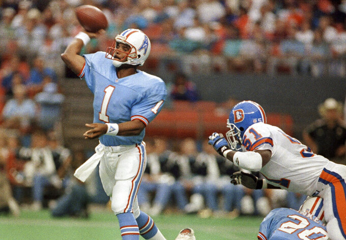 FILE - In this Oct. 7, 1991, file photo, Houston Oilers quarterback Warren Moon (1) throws a pass against the Denver Broncos during an NFL football game in Houston. Moon went undrafted after a stellar college career at Washington and was forced to play in Canada where he won two Grey Cup MVP awards in the CFL title game and was the most outstanding player in the league in 1983. He finally got his shot in the NFL the following year with Houston and went on to throw for 49,325 yards in a Hall of Fame career that would have been  even more prolific if he hadn't spent his first six seasons in Canada. (AP Photo, File)