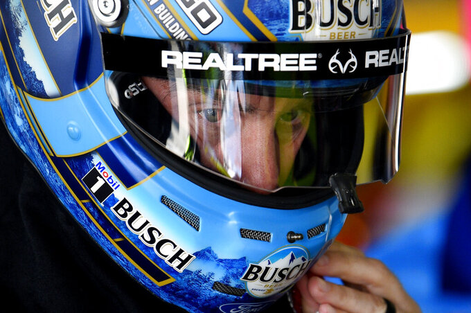 Kevin Harvick puts on his helmet before a practice session for Sunday's NASCAR Cup Series auto race, Saturday, July 27, 2019, in Long Pond, Pa. (AP Photo/Derik Hamilton)