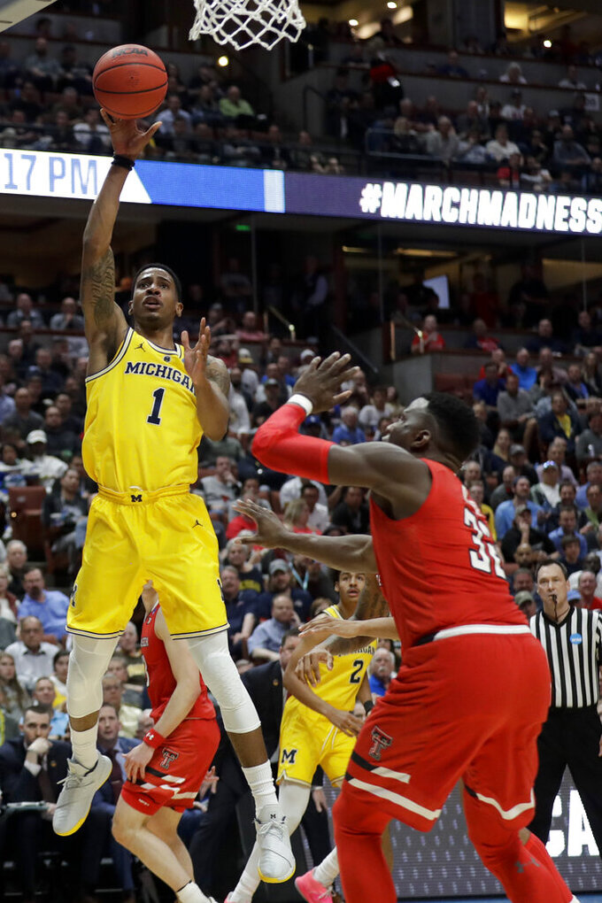 Michigan guard Charles Matthews, left, shoots over Texas Tech center Norense Odiase during the first half an NCAA men's college basketball tournament West Region semifinal Thursday, March 28, 2019, in Anaheim, Calif. (AP Photo/Marcio Jose Sanchez)