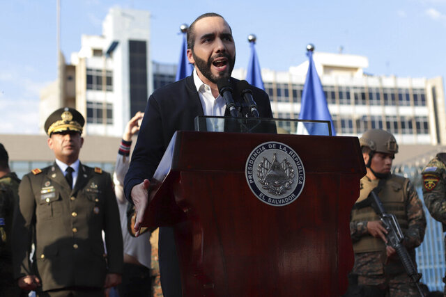 El Salvador's President Nayib Bukele, accompanied by members of the armed forces, speaks to his supporters outside Congress in San Salvador, El Salvador, Sunday, Feb. 9, 2020. Bukele has called on supporters to converge around the country's parliament after legislators refused to gather to vote on a $109 million loan to better equip the country's security forces. Top commanders of the country's police and military have expressed allegiance to the president during the standoff, while positioning security forces around the legislative building. (AP Photo/Salvador Melendez)