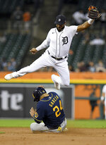Milwaukee Brewers' Avisaíl García slides under Detroit Tigers shortstop Jeimer Candelario on a steal of second base during the fourth inning of a baseball game in Detroit, Tuesday, Sept. 14, 2021. (AP Photo/Lon Horwedel)