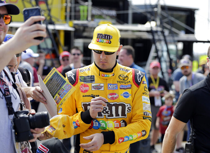 Kyle Busch signs autographs during qualifying for the NASCAR Cup Series auto race at the Homestead-Miami Speedway, Saturday, Nov. 17, 2018, in Homestead, Fla. (AP Photo/Terry Renna)