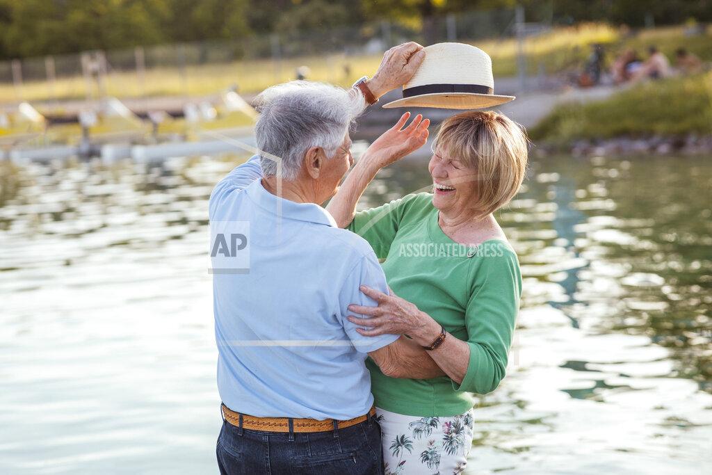 Senior man putting hat on cheerful woman by lake