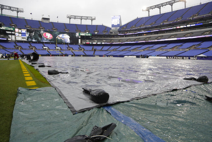 A tarp covers the field during rain showers in preparation for an NFL football game between the Baltimore Ravens and the San Francisco 49ers, Sunday, Dec. 1, 2019, in Baltimore, Md. (AP Photo/Julio Cortez)