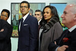 In this March 5, 2015 photo, Isabel dos Santos, reputedly Africa's richest woman, and her husband and art collector Sindika Dokolo, center left, attend the opening of an art exhibition featuring works from his collection in Porto, Portugal. On Monday, Jan. 6, 2020, Angolan Foreign Minister Manuel Augusto said that there is no political motivation behind the government's demand for more than $1 billion from dos Santos, her husband and a Portuguese business partner. Isabel dos Santos is a daughter of Jose Eduardo dos Santos, who ruled the oil- and diamond-rich nation for 38 years until 2017. (AP Photo/Paulo Duarte)