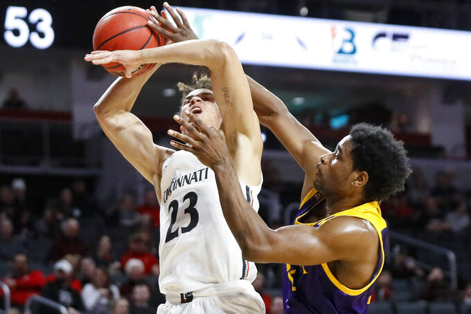 Cincinnati's Zach Harvey (23) is fouled on a shot by East Carolina's Bitumba Baruti, right, during the second half of an NCAA college basketball game, Sunday, Jan. 19, 2020, in Cincinnati. (AP Photo/John Minchillo)