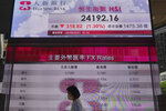 A woman wearing a face mask walks past a bank's electronic board showing the Hong Kong share index at Hong Kong Stock Exchange in Hong Kong Monday, Sept. 27, 2021. Asian share rose Monday, but skepticism about the economic outlook for the region tempered the rally amid worries about further waves of COVID-19 outbreaks. (AP Photo/Vincent Yu)