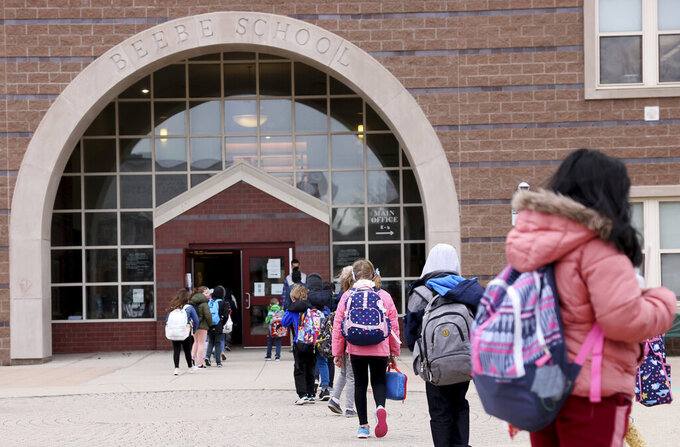 Students file into the Beebe School, in Malden, Mass., Monday, April 5, 2021, as they return to full-time in-person school. The majority of elementary schools in the state returned to full-time, in-person learning Monday. (Jessica Rinaldi/The Boston Globe via AP)