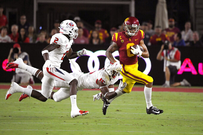Southern California wide receiver Michael Pittman Jr., right, runs the ball as Fresno State defensive back Chris Gaston, left, and linebacker Arron Mosby defend during the first half of an NCAA college football game Saturday, Aug. 31, 2019, in Los Angeles. (AP Photo/Mark J. Terrill)