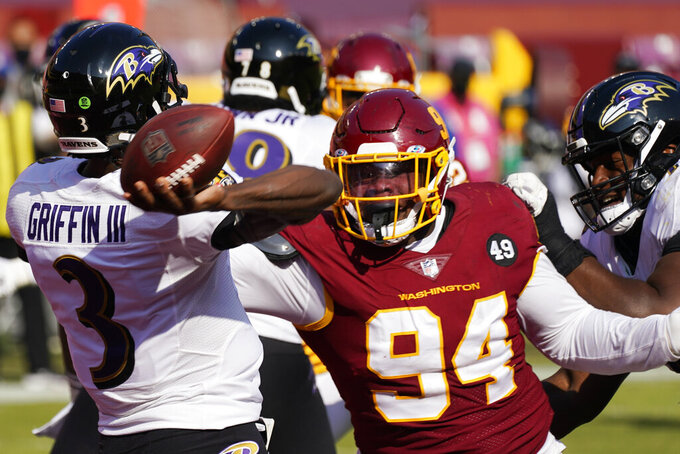 Baltimore Ravens quarterback Robert Griffin III (3) throws the ball for an interception under pressure from Washington Football Team defensive tackle Daron Payne (94) during the second half of an NFL football game, Sunday, Oct. 4, 2020, in Landover, Md. (AP Photo/Steve Helber)