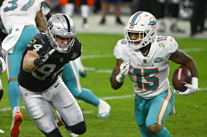 Miami Dolphins running back Lynn Bowden (15) runs by Las Vegas Raiders defensive end Carl Nassib (94) during the first half of an NFL football game, Saturday, Dec. 26, 2020, in Las Vegas. (AP Photo/David Becker)