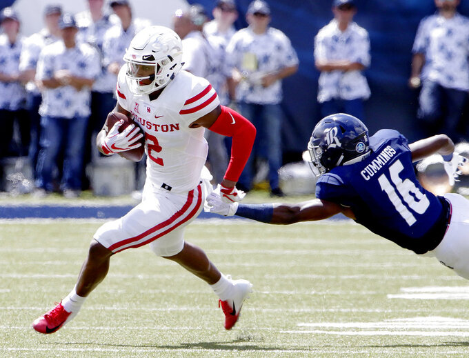 Houston wide receiver Keith Corbin (2) evade the tackle attempt by Rice defensive back Joshua Cummings (16) during the first half of a NCAA college football game Saturday, Sep. 1, 2018, in Houston. (AP Photo/Michael Wyke)