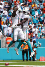 Miami Dolphins wide receiver Preston Williams (18) congratulates wide receiver DeVante Parker (11), after Parker scored a touchdown, during the first half at an NFL football game against the Los Angeles Chargers, Sunday, Sept. 29, 2019, in Miami Gardens, Fla. AP Photo/Wilfredo Lee)