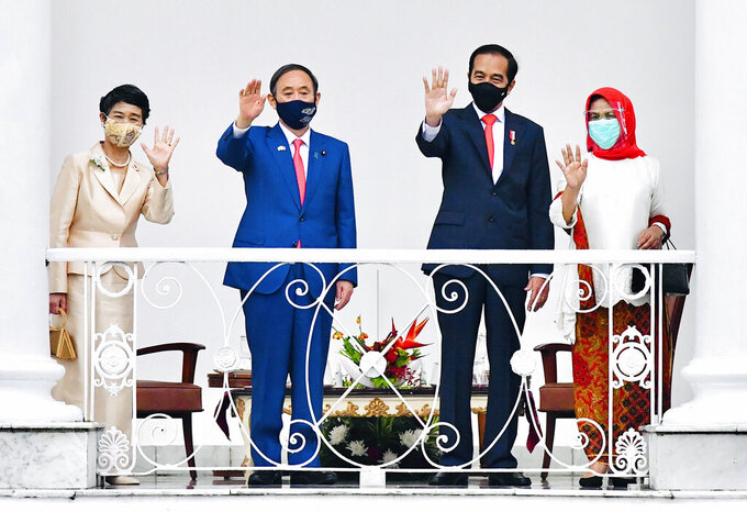 In this photo released by Indonesian Presidential Palace, Japanese Prime Minister Yoshihide Suga, second left, Indonesian President Joko Widodo, second right, Suga's wife Mariko, left, and Widodo's wife Iriana wave during their meeting at the Presidential Palace in Bogor West Java, Indonesia, Tuesday, Oct 20, 2020. (Laily Rachev/Indonesian Presidential Palace via AP)