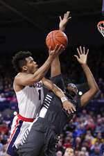 Gonzaga guard Admon Gilder, left, shoots around Santa Clara center Jaden Bediako during the first half of an NCAA college basketball game in Spokane, Wash., Thursday, Jan. 16, 2020. (AP Photo/Young Kwak)