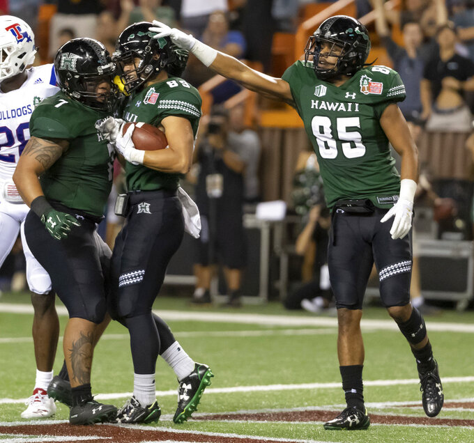 Hawaii running back Dayton Furuta (7) and wide receiver Marcus Armstrong-Brown (85) celebrate a touchdown by wide receiver Jason-Matthew Sharsh (89) in the first half of the Hawaii Bowl NCAA college football game, Saturday, Dec. 22, 2018, in Honolulu. (AP Photo/Eugene Tanner)