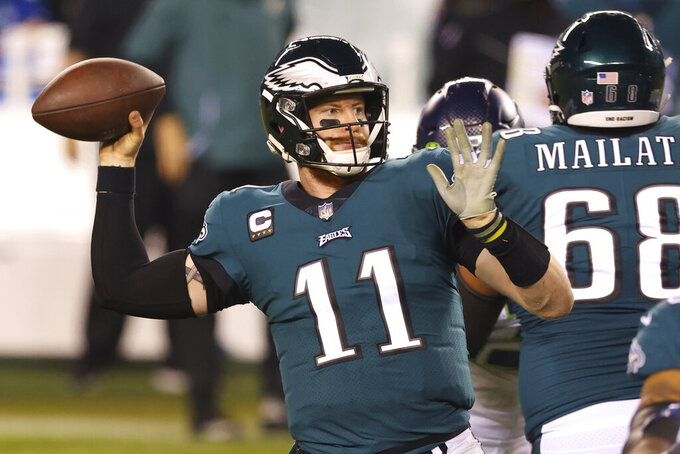 FILE - Philadelphia Eagles' Carson Wentz (11) passes during an NFL football game against the Seattle Seahawks in Philadelphia, in this Monday, Nov. 30, 2020, file photo. Jettisoning a veteran player often comes with a price in the NFL, and not just because of the loss of skill and experience. In most cases, these annual late-winter moves leave a team trying to create more space under the salary cap with a certain amount of dead money. That can put the squeeze on free agent pursuits. The Philadelphia Eagles are the extreme example this year with a $33.8 million charge for trading quarterback Carson Wentz.(AP Photo/Rich Schultz, File)
