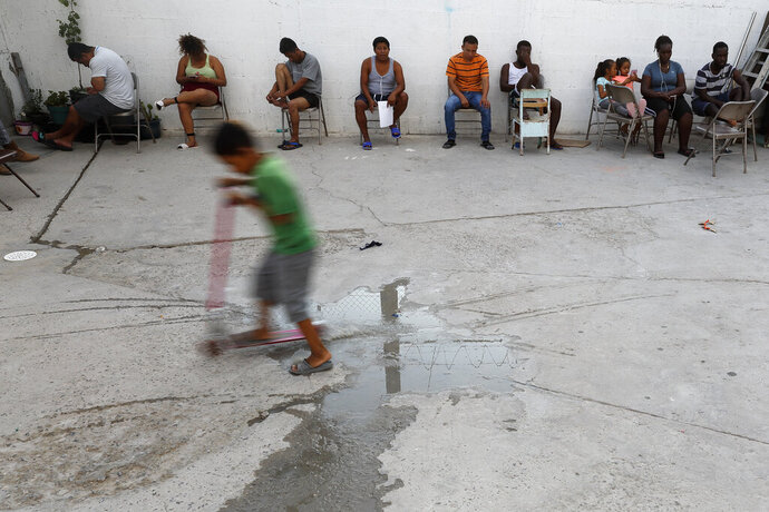 In this July 26, 2019, photo, people from Africa and Central America sit in chairs as the sun sets at El Buen Pastor shelter for migrants in Cuidad Juarez, Mexico. (AP Photo/Gregory Bull)