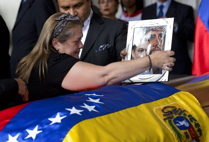 Luz Alban, the sister of opposition activist Fernando Alban places a framed portrait of her brother shadowed by an image of Jesus Christ over the flag-draped casket containing his remains, during a solemn ceremony at the National Assembly headquarters, in Caracas, Venezuela, Tuesday, Oct. 9, 2018. International condemnation of Venezuela's leadership poured in Tuesday following the suspicious death of the opposition activist authorities say evaded justice by throwing himself from the 10th floor of a police building. (AP Photo/Ariana Cubillos)