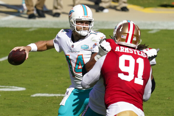 Miami Dolphins quarterback Ryan Fitzpatrick (14) passes as San Francisco 49ers defensive end Arik Armstead (91) applies pressure during the first half of an NFL football game in Santa Clara, Calif., Sunday, Oct. 11, 2020. (AP Photo/Tony Avelar)