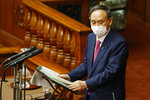 Japanese Prime Minister Yoshihide Suga, wearing a face mask, delivers a speech at the parliamentary session at the Upper House in Tokyo, Friday, Jan. 22, 2021. Japan is accelerating preparations for COVID-19 vaccinations in hopes of starting them in late February, but uncertainty is growing as the country faces vaccine-shy public, slow approval process and bureaucratic roadblocks, casting a doubt if Tokyo Olympic this summer is possible.(Masanori Takei/Kyodo News via AP)