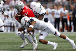 Ohio State quarterback Justin Fields, left, is tackled by Cincinnati defensive lineman Curtis Brooks, right, and defensive back Darrick Forrest during the first half of an NCAA college football game Saturday, Sept. 7, 2019, in Columbus, Ohio. (AP Photo/Jay LaPrete)
