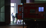 Medical staff in carry the first person infected with the coronavirus in the German state of North Rhine Westphalia out of an ambulance into the Infection Center of the University Hospital in Duesseldorf, Germany, Wednesday, Feb 26, 2020. (Guido Kirchner/dpa via AP)