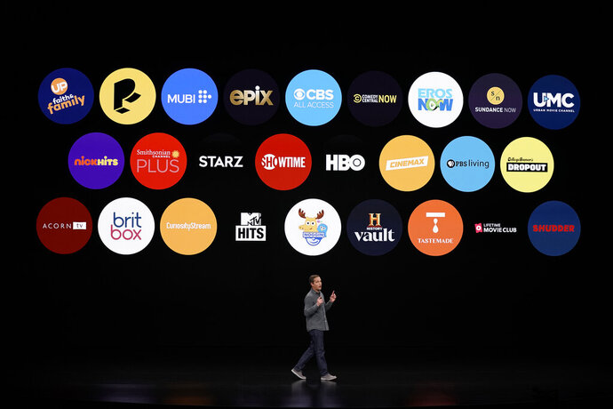 FILE - In this March 25, 2019, file photo Peter Stern, Apple Vice President of Services, speaks at the Steve Jobs Theater during an event to announce new products in Cupertino, Calif. Apple TV Plus launches on Friday for $5 a month with just eight shows and a few more coming soon. Apple will bundle it with sales of new gadgets like the iPhone, Mac and Apple TV. That suggests a market of 40 million customers, said Wedbush analyst Dan Ives. (AP Photo/Tony Avelar, File)