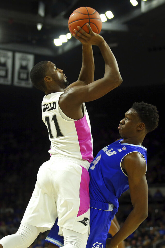 Providence's Alpha Diallo (11) shoots over Seton Hall's Tyrese Samuel (4) during the second half of an NCAA college basketball game Saturday, Feb. 15, 2020, in Providence, R.I. (AP Photo/Stew Milne)