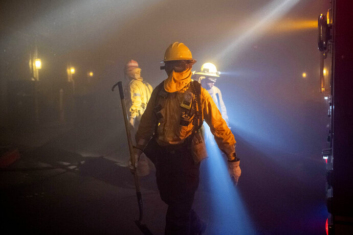 In this Thursday, Oct. 10, 2019 photo, firefighters check on homes in smoke from the Saddleridge fire in Sylmar, Calif. (AP Photo/Michael Owen Baker)