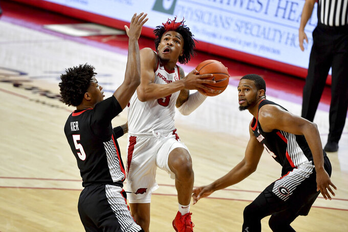 Arkansas guard Desi Sills (3) tries to drive past Georgia defenders Justin Kier (5) and P.J. Horne (24) during the second half of an NCAA college basketball game Saturday, Jan. 9, 2021, in Fayetteville, Ark. (AP Photo/Michael Woods)